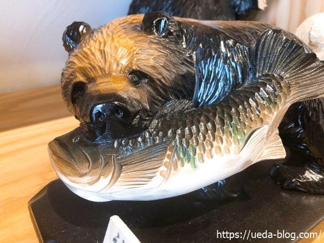 ポロトミンタラ 鮭を咥えた熊の彫刻物